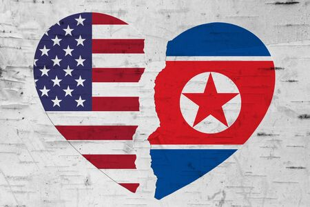 USA and North Korea flags in a broken heart over weathered wood