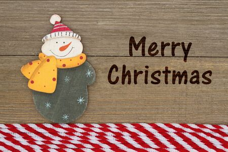 Old fashion Christmas greeting, A retro snowman on weathered wood background with text Merry Christmas Stock Photo