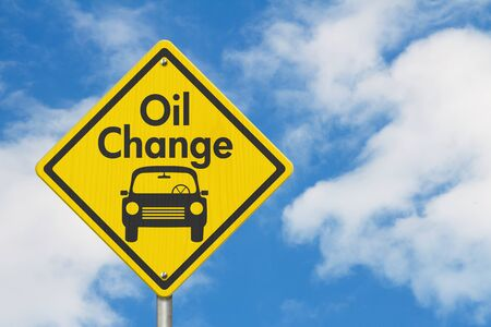 Oil change with car on yellow warning highway road sign with sky background