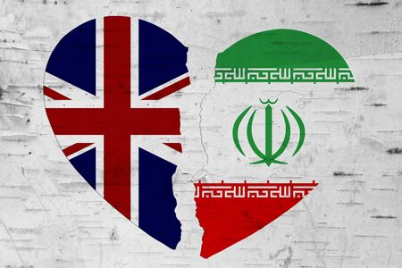 British and Iran flags in a broken heart over weathered wood