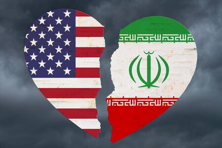 USA and Iran flags in a broken heart with stormy sky background Imagens - 128583839