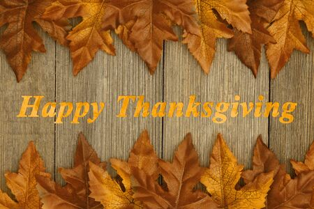 Happy Thanksgiving greeting with fall leaves on weathered wood