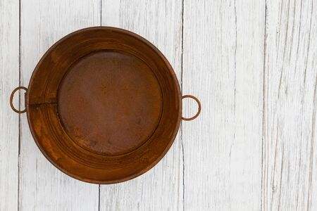 Rusted tin pail on weathered whitewash textured wood background with copy space for your message