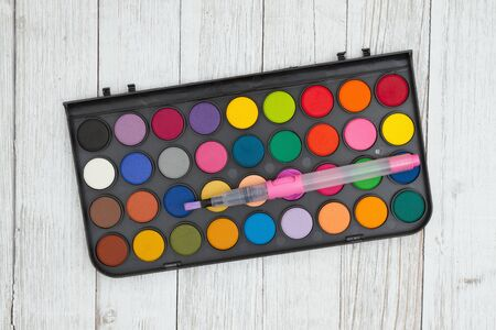 Colorful watercolor paint kit with brush on whitewash textured weathered wood Stockfoto