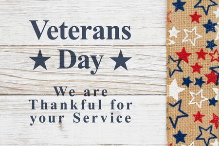 Veterans Day message with red, white and blue stars on burlap on a weathered whitewash wood