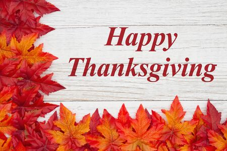 Happy Thanksgiving greeting with red and orange fall leaves on weathered whitewash wood textured Stock Photo