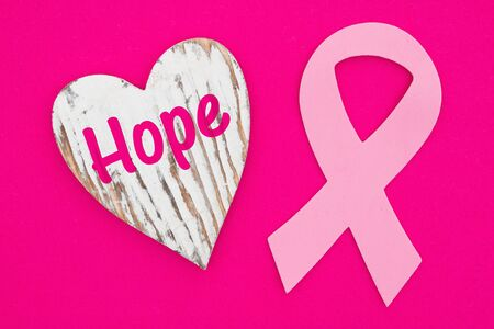Hope message on weathered heart with pink cancer ribbon on bright pink textured felt material