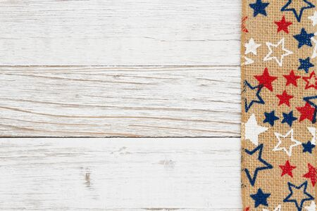Red, white and blue stars on burlap on a weathered whitewash wood background with copy space for your message