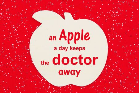 An apple a day keeps the doctor away message with a wood apple on a red felt sparkle fabric