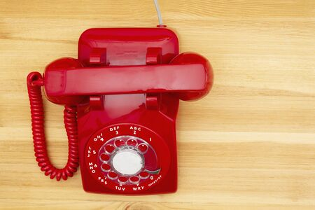 Red old retro rotary landline phone on a wood desk Banque d'images - 131535211
