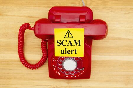 Scam alert message on a sticky note on a red old retro rotary landline phone on a wood desk