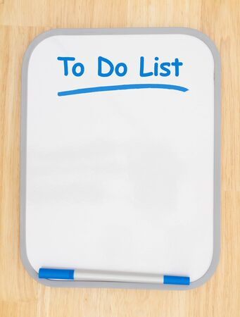 To do list on white dry erase board with marker on wood textured wall with copy space for your message