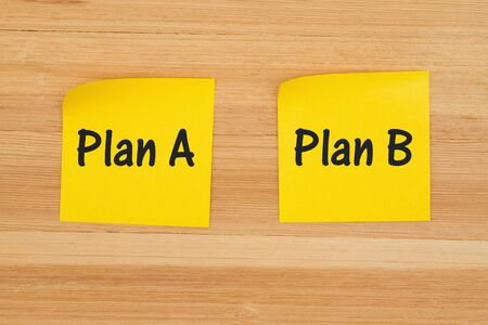 Plan A and Plan B for decisions on two sticky notes on textured wood desk