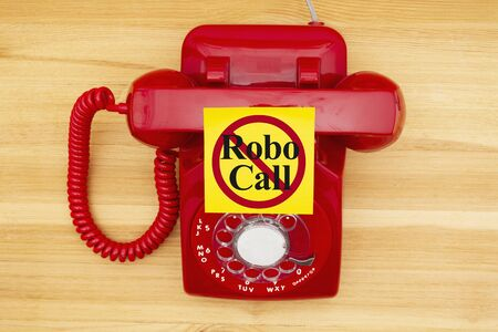 No Robo Call message on a sticky note on a red old retro rotary landline phone on a wood desk Stock Photo