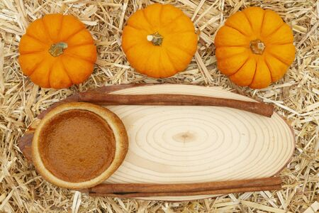 Pumpkin pie and pumpkins and spice with straw hay  with wood sign copy space for your message Stock Photo