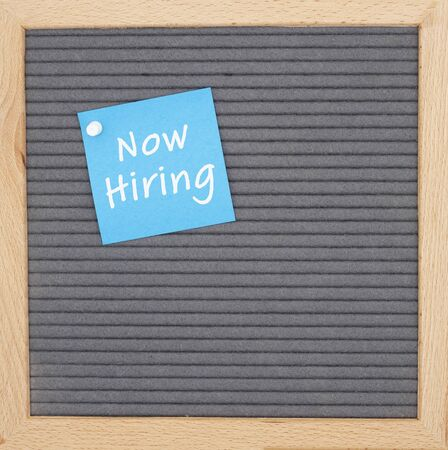 Now hiring message on sticky note on gray felt letter board with a wood frame