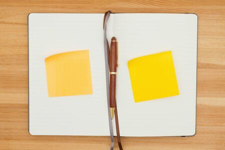Blank journal  with pen and  yellow sticky notes on a wood desk with copy space for your message