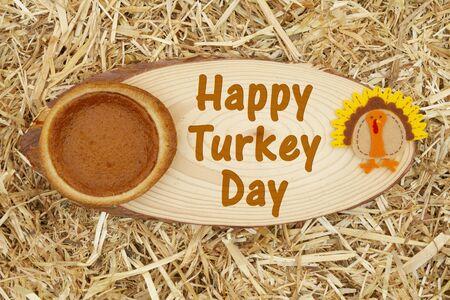 Happy Turkey Day message with pumpkin pie and a turkey with straw hay Stock fotó