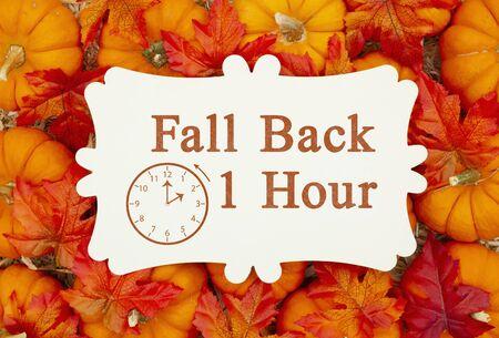 Fall Back 1 godzinna wiadomość o zmianie czasu na metalowej tabliczce na dyniach i słomianym sianie Zdjęcie Seryjne