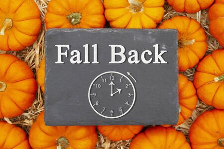 Fall Back 1 hour time change message on a chalkboard sign on pumpkins and a straw hay 版權商用圖片
