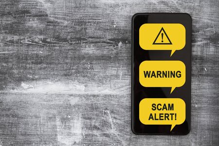 Scam Alert message on a screen of black cell phone on weathered black grunge wood