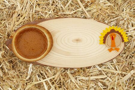 Pumpkin pie and a turkey straw hay background with wood sign copy space for your message Stock fotó