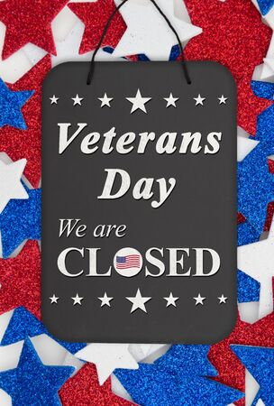 Veterans Day closed sign message on chalkboard with red, white and blue glitter stars
