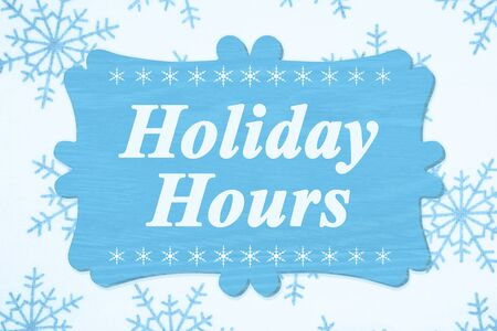 Holiday Hours message on a wood sign with a blue snowflakes Stock Photo