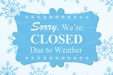 Sorry We're Closed Due to Weather message on a wood sign with a blue snowflakes