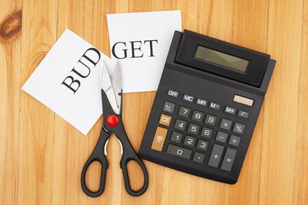 Cutting your monthly budget with a calculator with a display and word budget cut with scissors on wooden desk Stock Photo