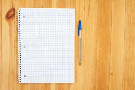 Notebook of blank graph paper and a pen on a wooden desk