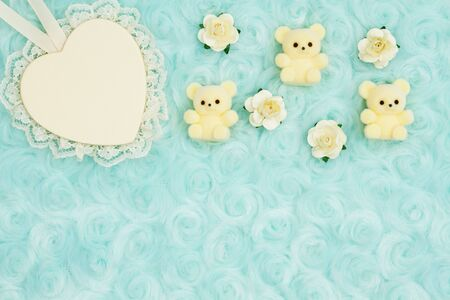 Wood heart with lace and teddy bears on pale teal rose plush fabric background with muted mix of shades to provide copy-space for your message Banco de Imagens