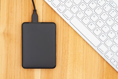 Black portable hard drive with a keyboard on a wooden desk Stock Photo