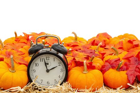Retro alarm clock with orange pumpkins with fall leaves on straw hay isolated over white with copy space for your message