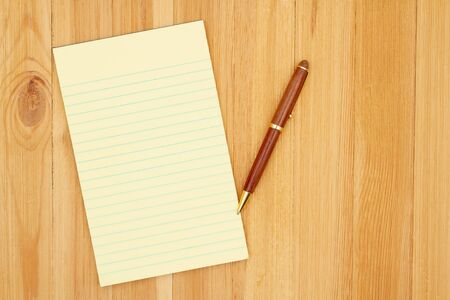 Yellow legal lined notepad paper with a pen on pine wood desk with copy space for your business or writing message or mockup Foto de archivo