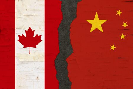Canadian and Chinese flags that are torn apart with dark separation material 写真素材