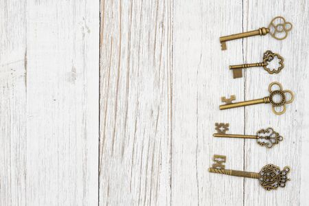 Skeleton keys on weathered whitewash wood background with grain texture with copy space for your security or lock message