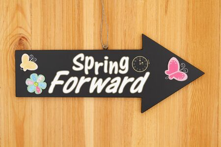 Spring Forward type message on hanging arrow chalkboard sign with a flower, clock and butterfly Stock Photo