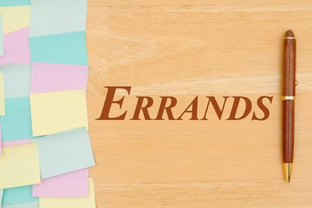 Errands type message with multi-color sticky note and a pen on a wood desk