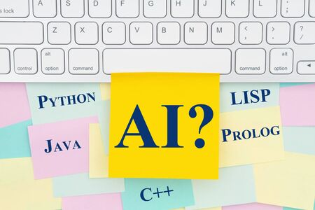 AI artificial intelligence programming languages type message on a sticky note on a computer keyboard with a bunch of paper Foto de archivo