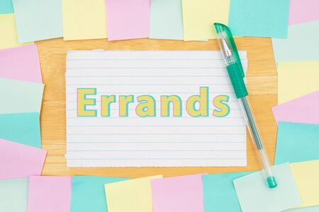 Errands type message on lined paper with multi-color sticky notes and a pen on a wood desk