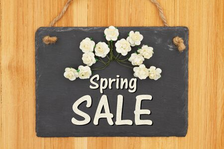 Spring Sale type message on a hanging chalkboard sign with white roses on wood Stock Photo