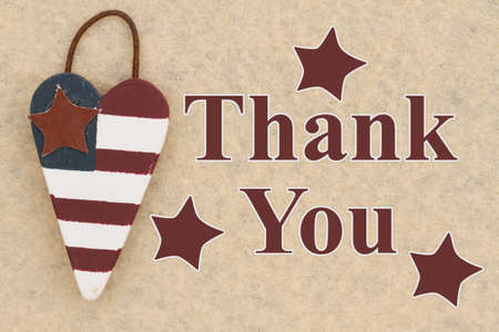 Thank you word message with retro USA stars and stripes flag wood heart on beige material 免版税图像