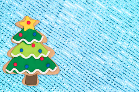Gingerbread Christmas tree on blue sparkle background with copy space for Christmas or holiday message Foto de archivo - 151338482