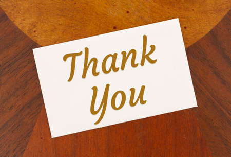 Thank you word message on white greeting card on light and dark wood