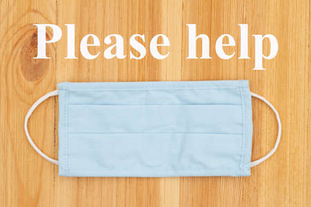 Please help word message on blue cloth face mask on a wood desk for your covid-19 message Stock Photo