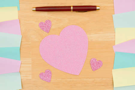 Multi-color sticky notes with a pen and a heart on a wood desk with copy space for your office or reminder message