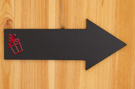 Christmas blank hanging arrow chalkboard sign with a present sign on wood with copy space for your xmas or holiday message