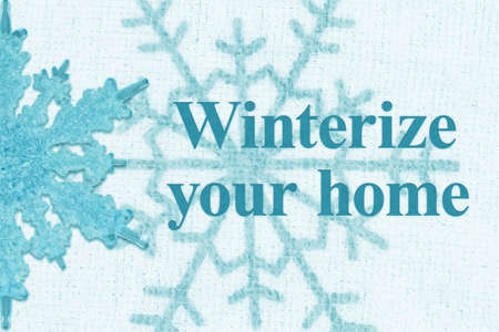 Winterize your home word message with blue snowflake on white fabric Stock Photo