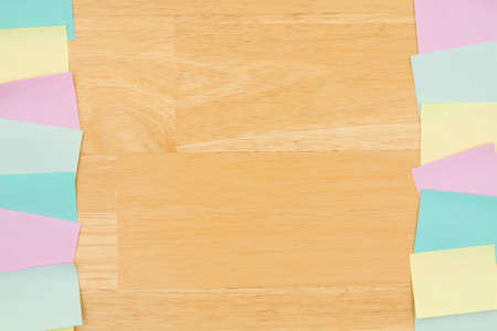 Sticky note background with multi-color notes on a wood desk wood with copy space for your office or reminder message